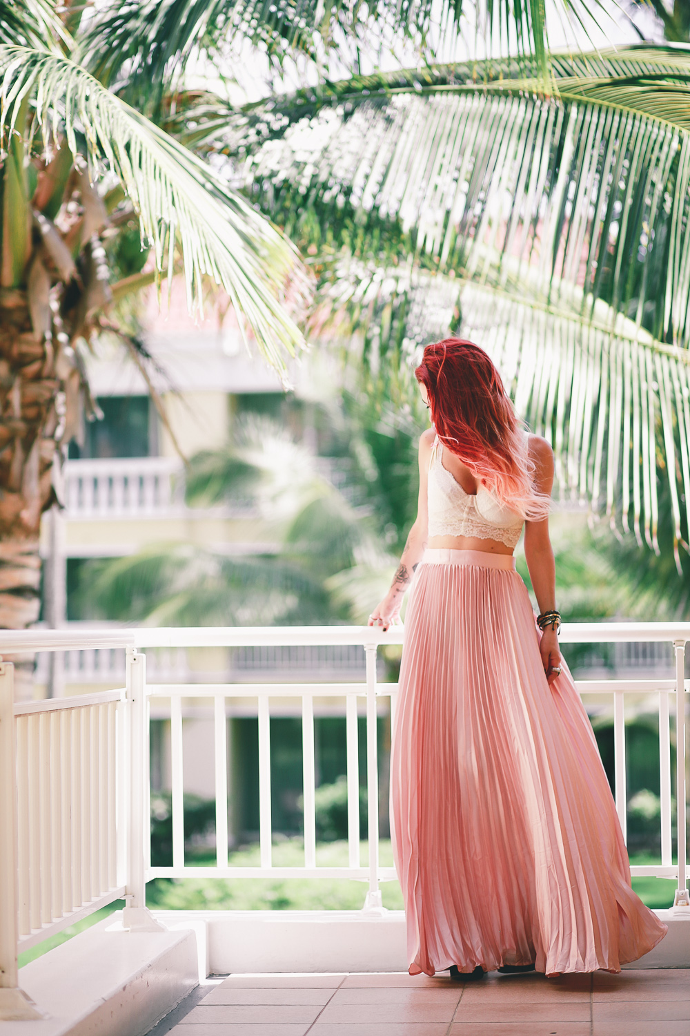 Le Happy wearing pastel pleated skirt and lace bustier in summer