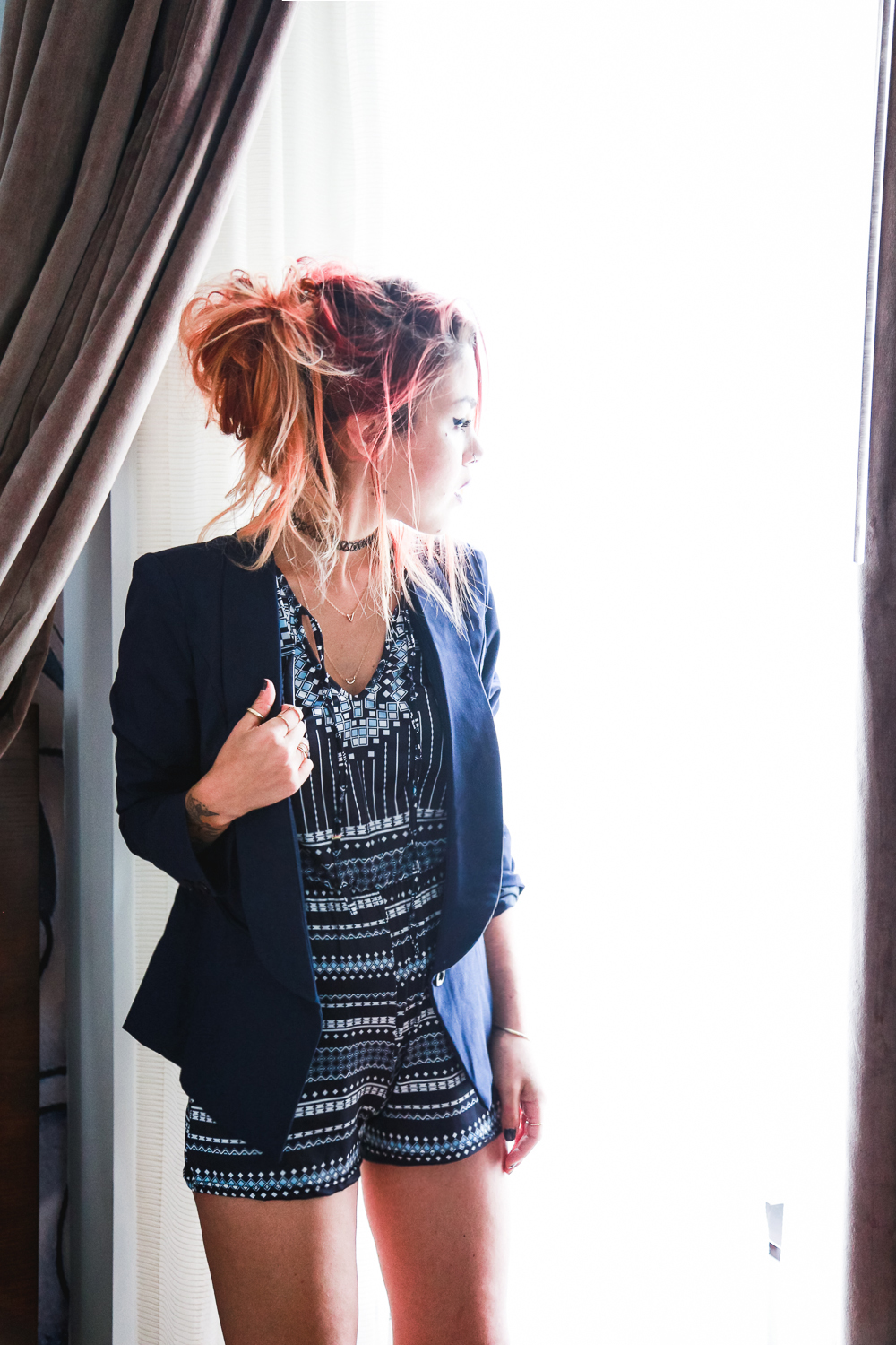 Le Happy wearing blue blazer and dressy printed romper