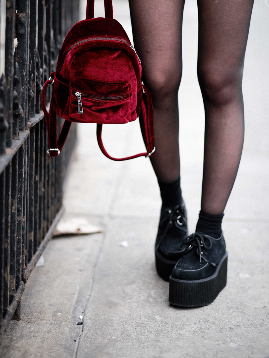 Le Happy wearing creepers and mini suede backpack