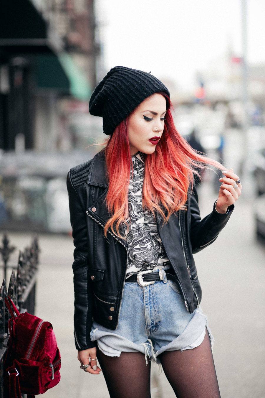 Le bahagia memakai celana pendek denim vintage dan biker jacket