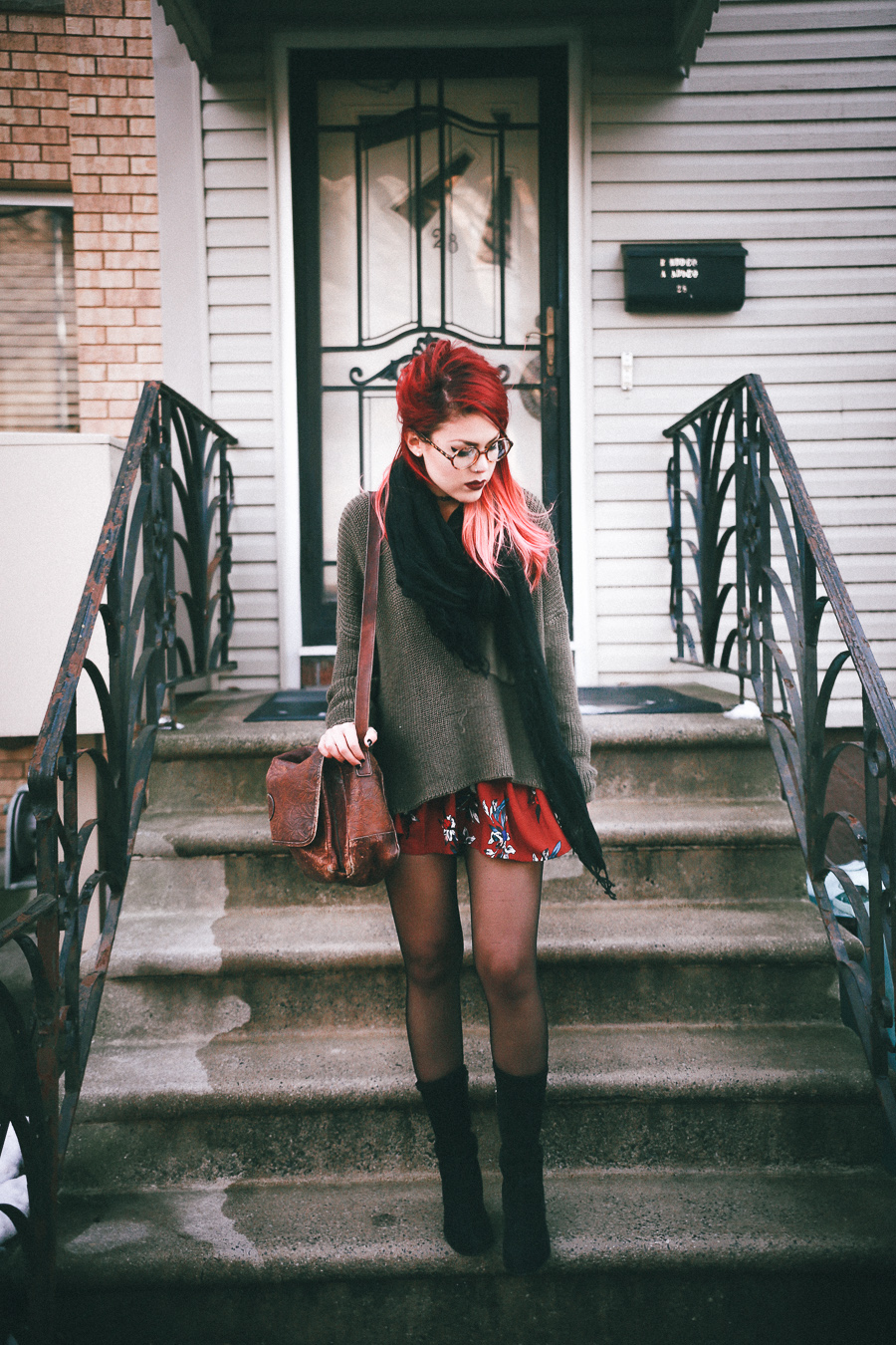Le Happy wearing chunky green sweater with a red floral dress and suede booties