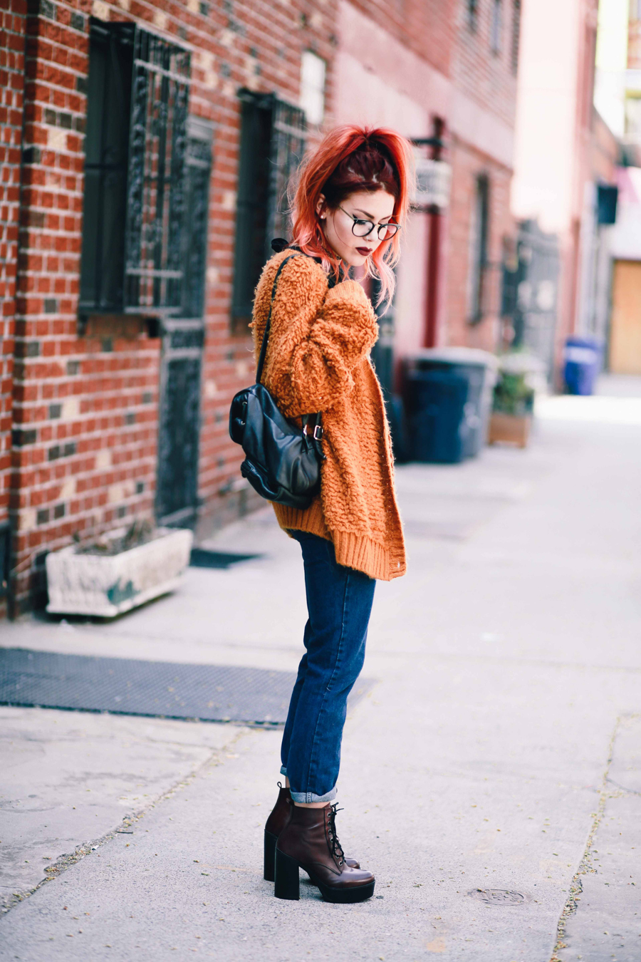 Le Happy wearing chunky sweater and Steve Madden red booties