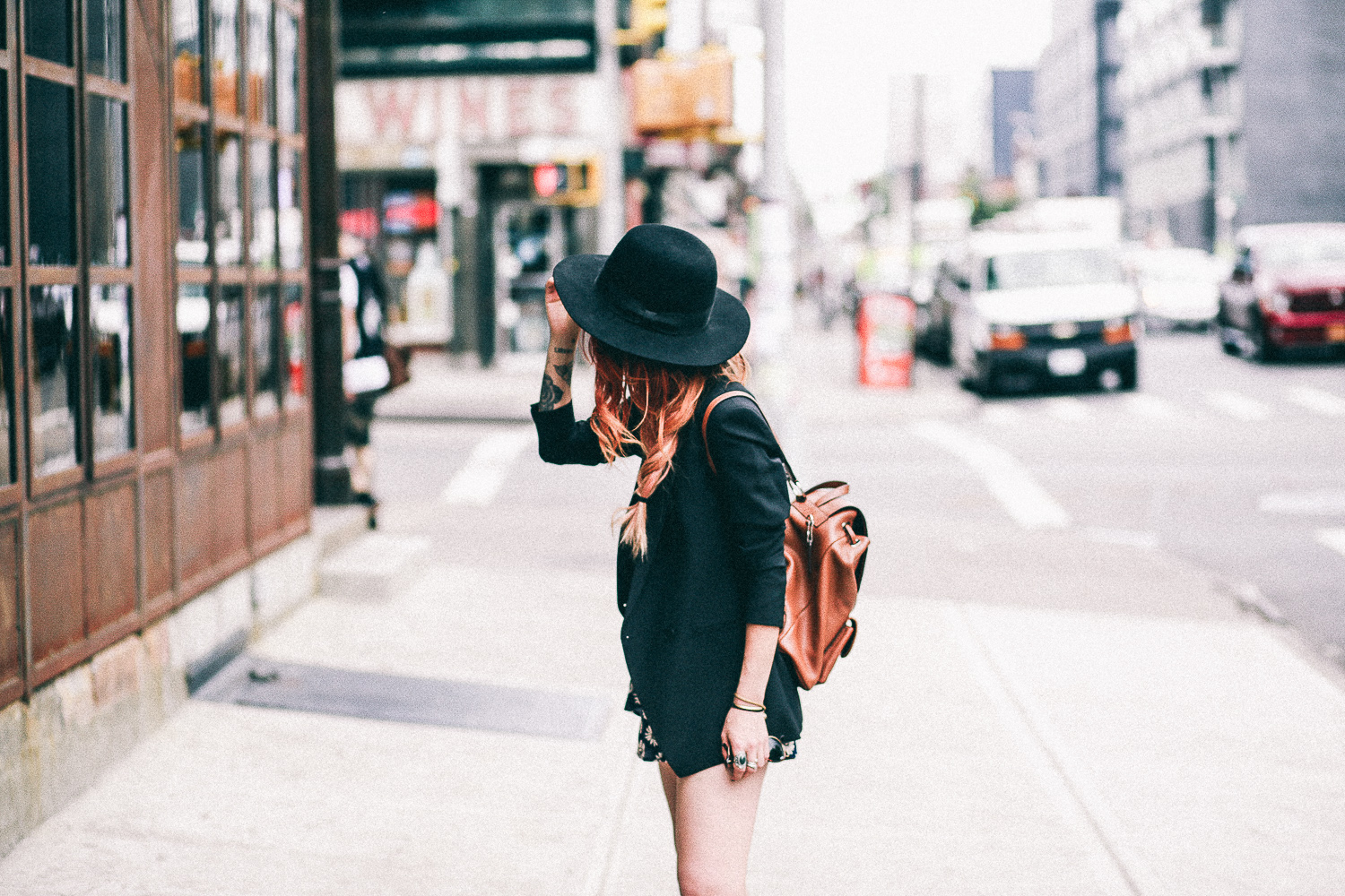 Le Happy wearing Coach camel backpack and Theory black blazer