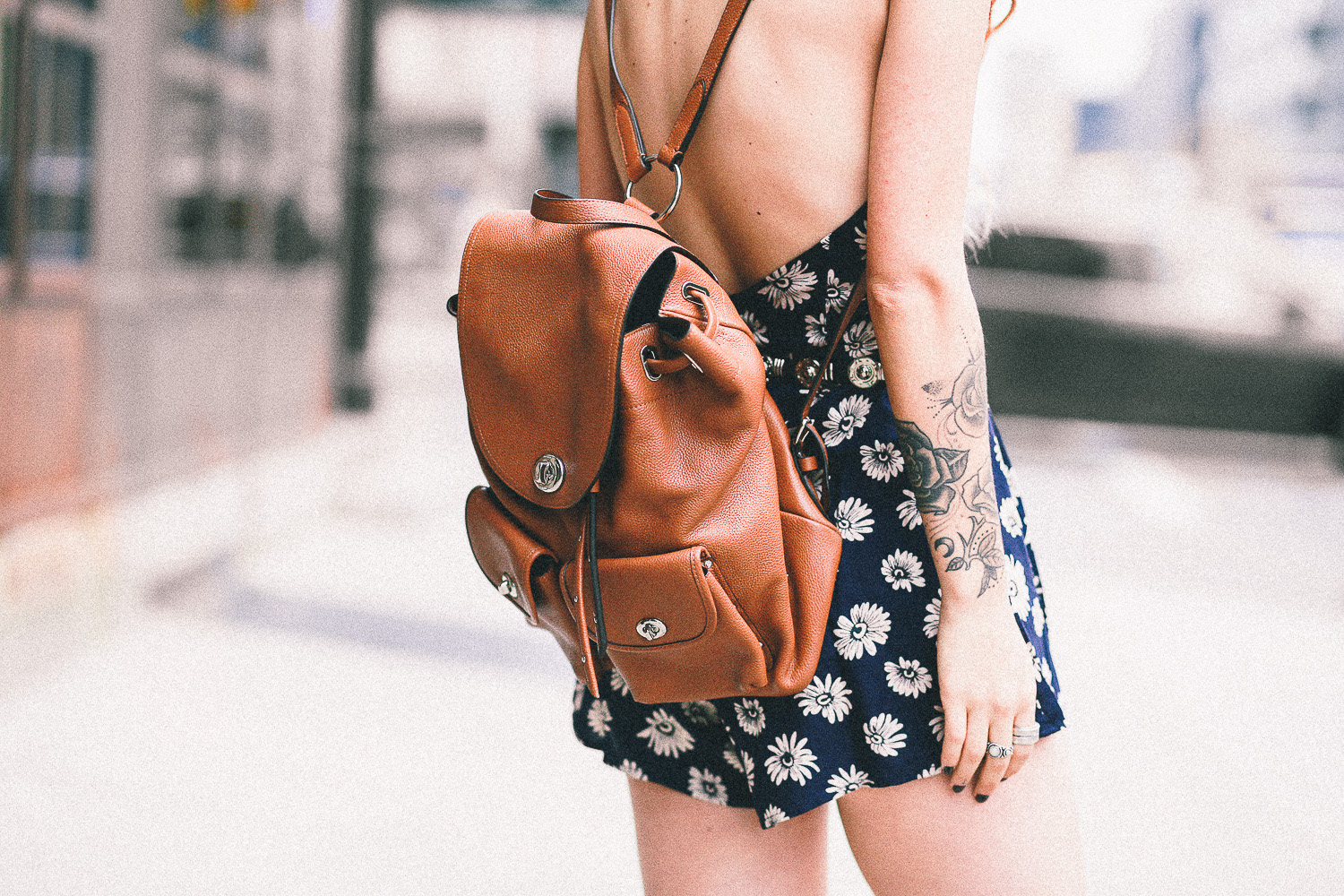 Le Happy wearing Coach camel backpack