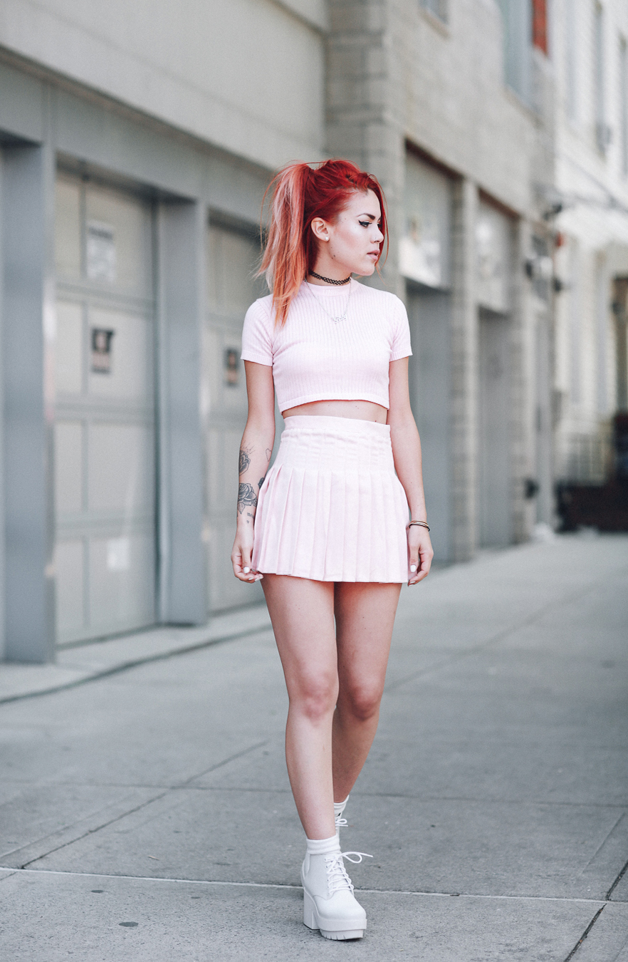 Le Happy wearing a pastel pink tennis skirt and unif crop top