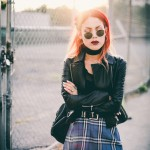 Le Happy wearing tartan skirt with round sunglasses and Elizabeth and James leather jacket